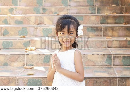 Asian Little Girl Was Wearing A White Shirt And White Flowers Hanging Over Her Ears, Standing And Pa