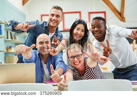 Successful business start-up team with thumbs up is happy