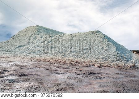 Brine Salt Farm With Sky And Clouds. Pile Of Organic Sea Salt. Raw Material Of Salt Industrial. Ocea