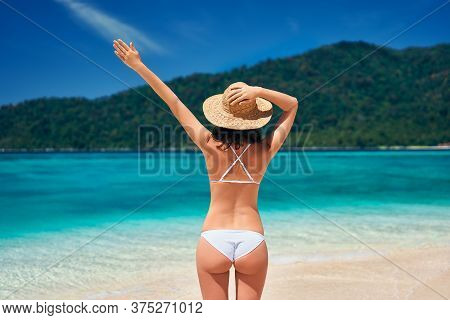 Back View Of Young Happy Woman In White Bikini And Straw Hat Raised Hand Up Enjoy Her Summer Vacatio