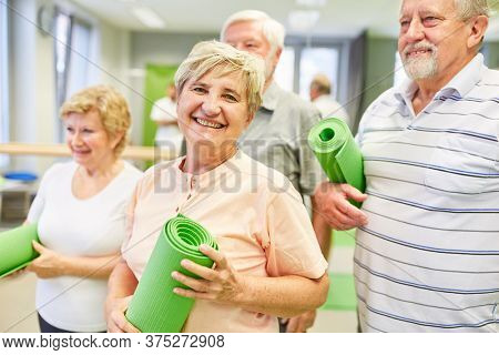 Happy senior woman with friends together in a gym class at the gym