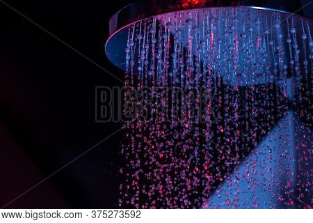 Drops Of Water Fall From A Watering Can In The Shower In Red-blue Light. Water Drops Close-up. Flow