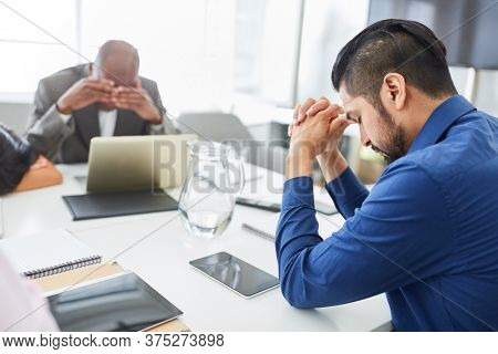 Desperate and sad business people sitting at conference table after bankruptcy or layoff