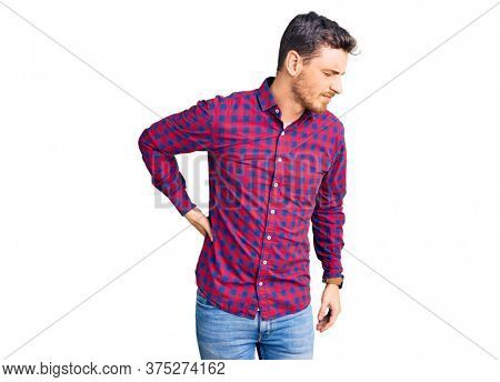 Handsome young man with bear wearing casual shirt suffering of backache, touching back with hand, muscular pain
