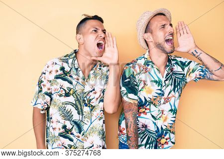 Young gay couple of two men wearing summer hat and hawaiian shirt shouting and screaming loud to side with hand on mouth. communication concept.