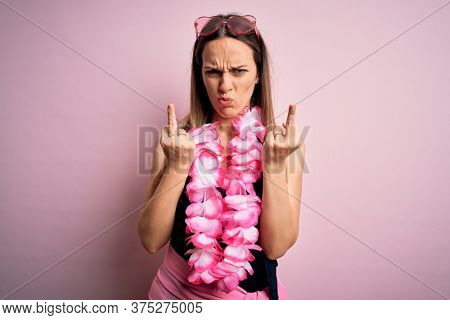 Young beautiful blonde woman wearing swimsuit and floral Hawaiian lei over pink background Showing middle finger doing fuck you bad expression, provocation and rude attitude. Screaming excited