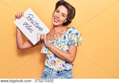 Young beautiful woman holding positive vibes banner looking positive and happy standing and smiling with a confident smile showing teeth