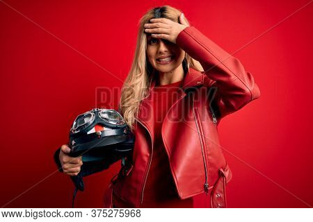 Young beautiful blonde motorcyclist woman holding moto helmet over isolated red background stressed with hand on head, shocked with shame and surprise face, angry and frustrated. Fear and upset