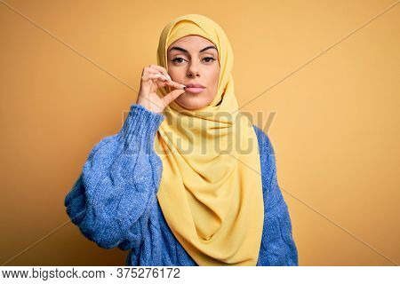 Young beautiful brunette muslim woman wearing arab hijab over isolated yellow background mouth and lips shut as zip with fingers. Secret and silent, taboo talking