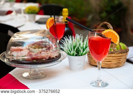 Aperitif in Italy. Delicious tasty traditional italian food and drink. Prosciutto, cheese, olives and cocktail in outdoor restaurant, cafe or pizzeria.