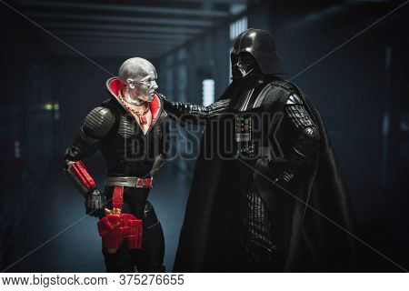 JULY 3 2020: Humor concept of Star Wars  Sith Lord Darth Vader recruiting Cobra crime boss Destro from the GI Joe comic - Hasbro action figures
