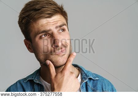 Portrait of redhead puzzled man posing and thinking at camera isolated over grey background