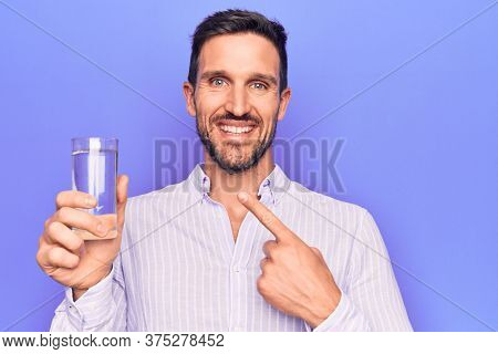 Young handsome man drinking glass of water to refreshment over isolated purple background smiling happy pointing with hand and finger