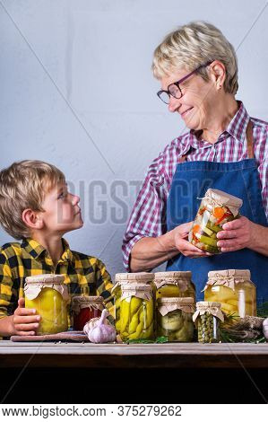 Senior Mature Woman With Grandson Holding In Hands Preserved Food