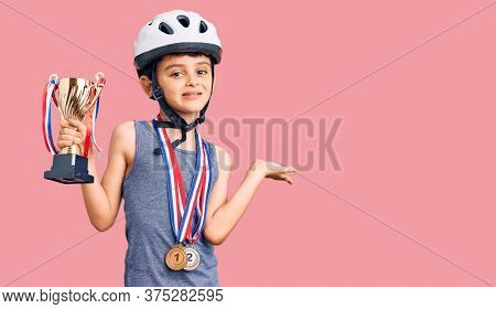 Little cute boy kid wearing bike helmet and winner medals holding winner trophy celebrating victory with happy smile and winner expression with raised hands