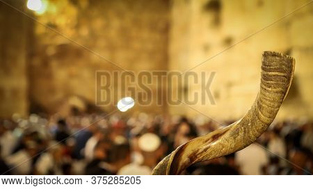 Shofar And In The Background, Religious People Pray At The Western Wall In The Holy City Of Jerusale