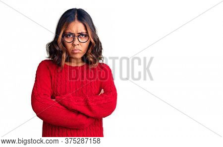 Young beautiful mixed race woman wearing red sweater and glasses skeptic and nervous, disapproving expression on face with crossed arms. negative person.
