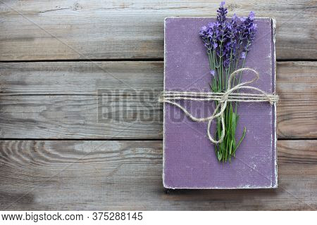 Old Book Decorated With Lavender Flowers And Tied With Jute Twine On Wooden Table. Copy Space. Selec