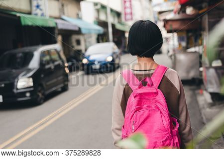 rear view of traveling woman with bag in the traditional marketplace at Taiwan