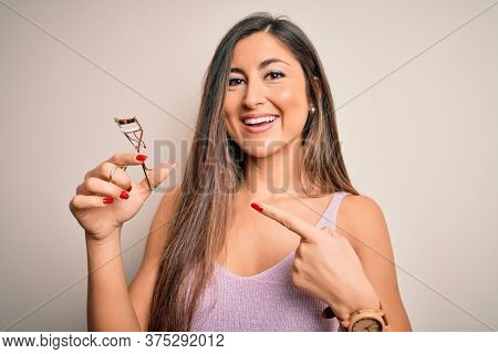 Young beautiful brunette woman holding eyelash curler over isolated white background very happy pointing with hand and finger