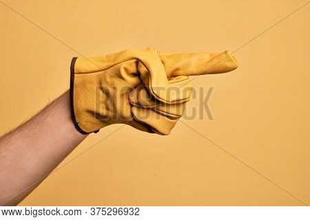 Hand of caucasian young man with gardener glove over isolated yellow background pointing with index finger to the side, suggesting and selecting a choice