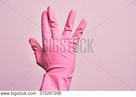 Hand of caucasian young man with cleaning glove over isolated pink background greeting doing Vulcan salute, showing back of the hand and fingers, freak culture
