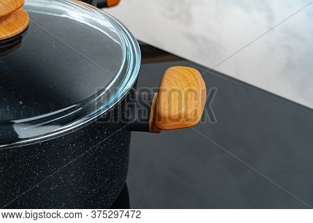 Black Cookware On Induction Stove Against Grey Wall
