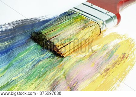 A Large Wooden Art Brush Paints On Canvas. Drawing Technique. Bright Colors On The Canvas. Hobbies A