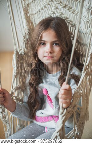 A Beautiful Young Dark-haired Girl In Gray Pajamas Relaxes In A Swing. Cute Brunette Girl Swinging I