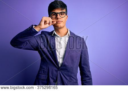 Young handsome business man wearing jacket and glasses over isolated purple background mouth and lips shut as zip with fingers. Secret and silent, taboo talking