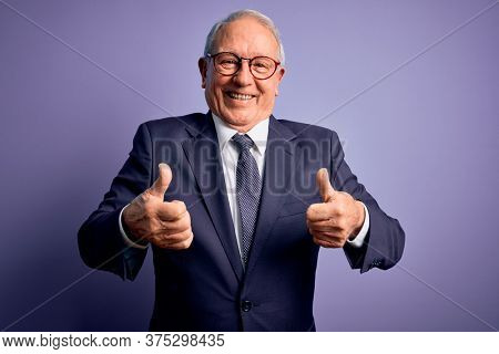 Grey haired senior business man wearing glasses and elegant suit and tie over purple background success sign doing positive gesture with hand, thumbs up smiling and happy. Cheerful expression.