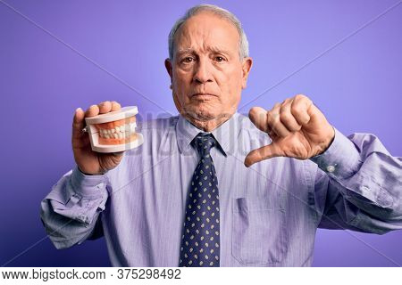 Grey haired senior man holding orthodontic prosthesis denture over purple background with angry face, negative sign showing dislike with thumbs down, rejection concept
