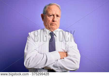 Grey haired senior business elegant man standing over purple isolated background skeptic and nervous, disapproving expression on face with crossed arms. Negative person.