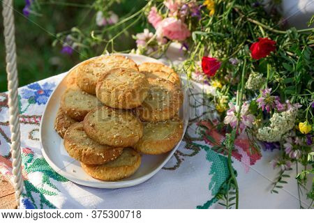 Shortbread Cookies With Blue Cheese And Sesame Seeds And A Wreath Of Wildflowers On A Swing. Rustic