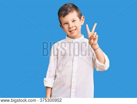 Cute blond kid wearing elegant shirt showing and pointing up with fingers number two while smiling confident and happy.