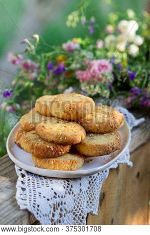 Shortbread Cookies With Blue Cheese And Sesame Seeds And A Wreath Of Wildflowers On A Summer Terrace