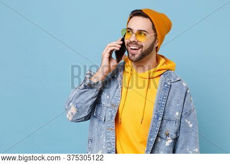Cheerful Young Hipster Guy In Fashion Jeans Denim Clothes Posing Isolated On Pastel Blue Background