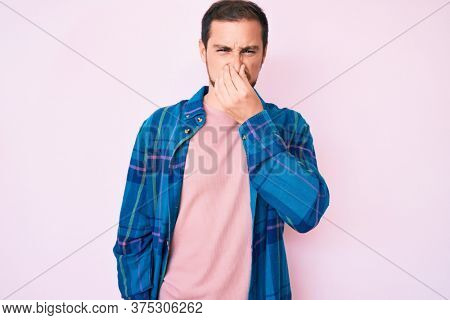 Young handsome man wearing casual clothes smelling something stinky and disgusting, intolerable smell, holding breath with fingers on nose. bad smell