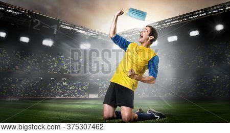Soccer or football player removing mask. Team sports player taking off medical mask and happily kneel on stadium. End of coronavirus outbreak.