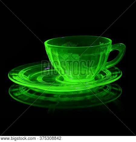 A Glowing Uranium Glass Teacup And Saucer Under Ultraviolet Light To Reveal Its Unique Properties.