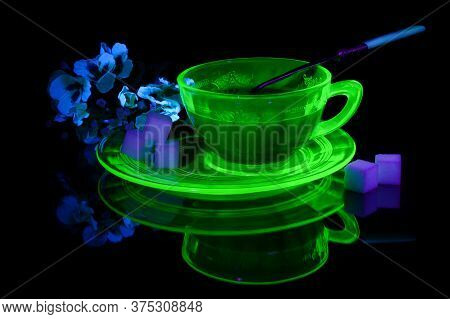 A Glowing Uranium Glass Teacup And Saucer Under Some Ultraviolet Light To Show Its Unique Properties