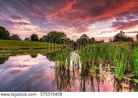 Beautiful sunset over the pond in Pruszcz Gdanski, Poland.