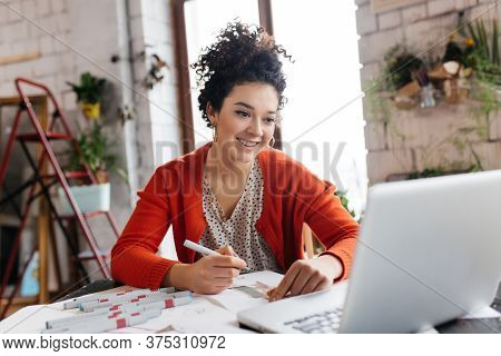 Young Smilng Woman With Dark Curly Hair Sitting At The Table Happily Working On Laptop Drawing Fashi