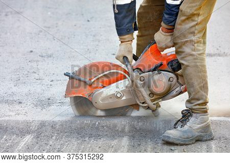 A Worker Mends Part Of The Road, Cuts Out Worn Asphalt In A Cloud Of Dust Using A Portable Concrete