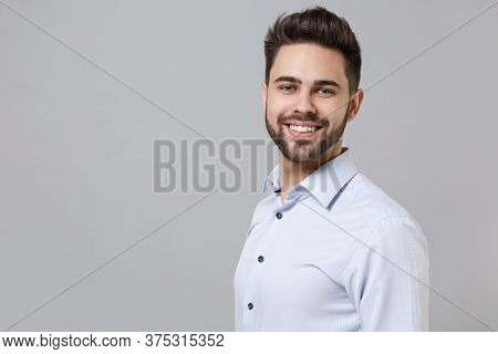 Side View Of Smiling Young Unshaven Business Man In Light Shirt Posing Isolated On Grey Wall Backgro