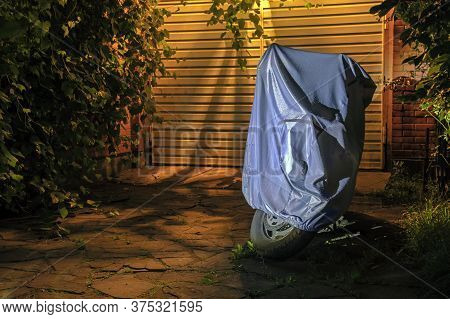 Motorcycle In Waterproof Sunshade Tent  Standing By The Garage Gate In The Night. Yellow Light Stree