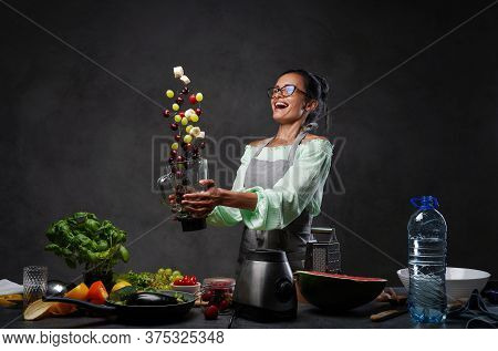 Emotional Mature Woman In Apron Tossing Fresh Fruit In The Air From A Blender In Kitchen. Homemade H