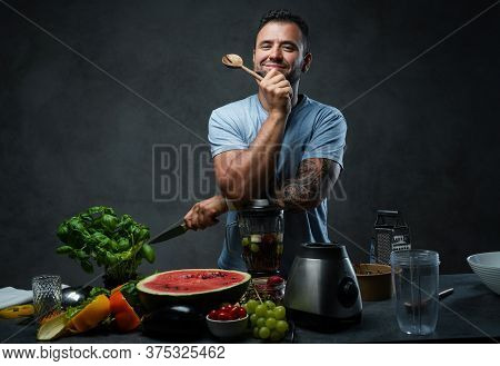 Handsome Tattooed Male In Blue Shirt Leaning On A Blender In Kitchen. Homemade Healthy Fruit Smoothi