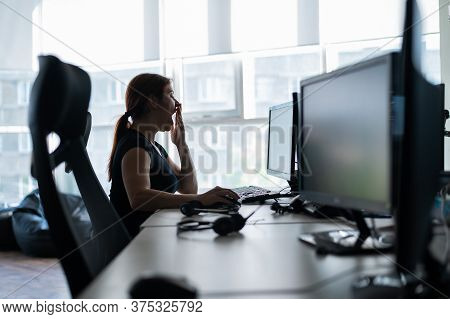 Tired Woman In A Black T-shirt Works In An Empty Office And Yawns At The Workplace. The Girl Works O
