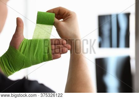 Man Rewinds His Hand With Bandage On An X-ray. Bandage For Inflammatory Processes And Seizures. Band